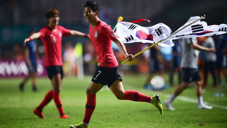 Son Heung-Min festeggia la vittoria nei giochi asiatici 2018 sventolando due bandiere della Corea del Sud. Foto: AFP.